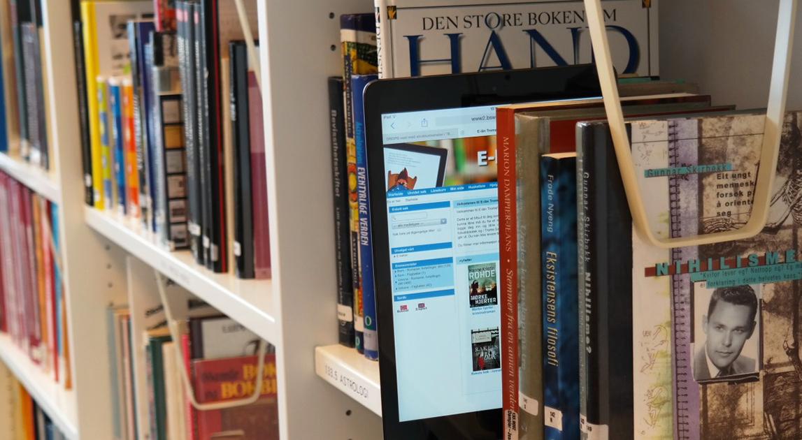 Utsnitt av bokhylle med bøker og e-lån på iPad